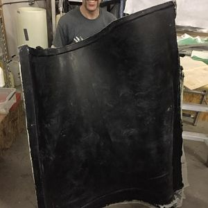 A happy helper holds a hefty helping of handcrafted cowling door mold.