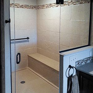 Custom corner shower with frameless glass enclosure and bench seat
