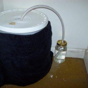 homemade fermenter has a black beach towel around it to keep out light
